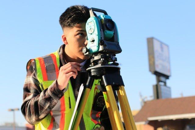 Construction surveyor using survey camera on a construction site